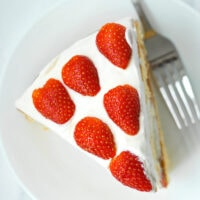 """Overhead view of a slice of Strawberry lemon Cream Cake on a plate with a fork. Text overlay """"Strawberry Lemon Cream Cake""""."""
