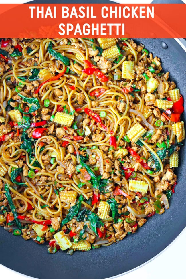 """Overhead view of large wok with spaghetti tossed with baby corn, green beans, holy basil, ground chicken, chilies, onion, and garlic in a brown sauce. Text overlay """"Thai Basil Chicken Spaghetti""""."""