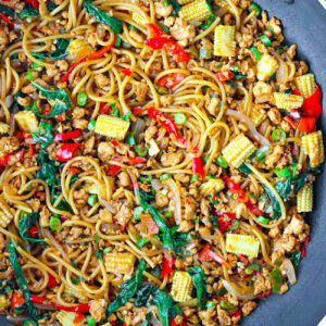 Top view of large wok with spaghetti tossed with ground chicken, red and green chilies, garlic, onion, baby corn, green beans, and holy basil in a brown sauce.