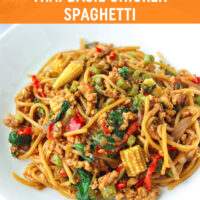 """Two diagonally placed white round plates with spaghetti tossed with ground chicken, garlic, red and green chilies, onion, baby corn, green beans, and holy basil in a brown sauce. Fork and spoon to the side of the plates. Text overlay """"Thai Basil Chicken Spaghetti""""."""
