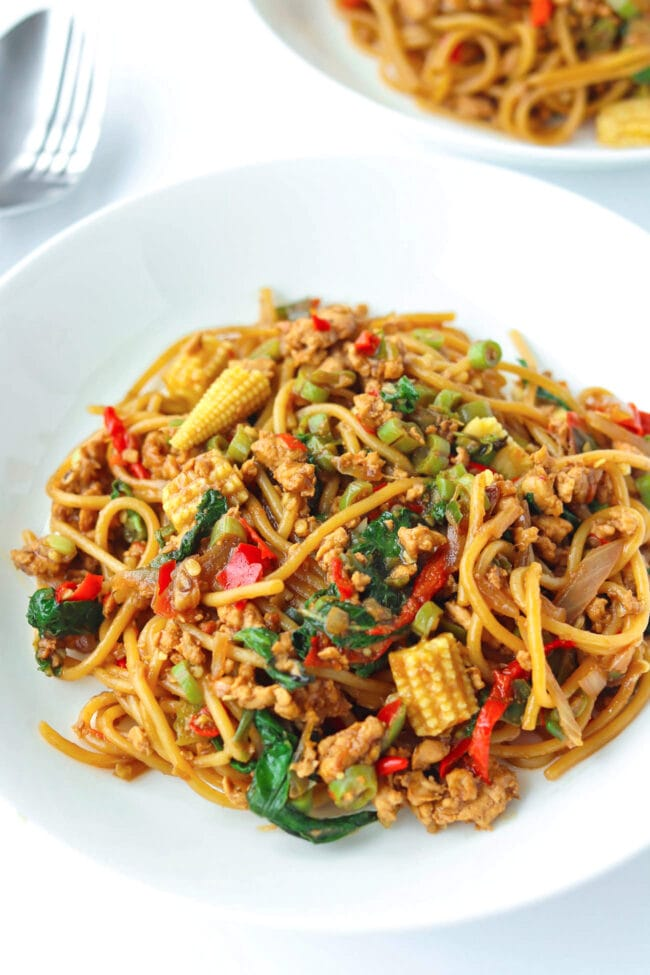 Two diagonally placed white round plates with spaghetti tossed with ground chicken, garlic, red and green chilies, onion, baby corn, green beans, and holy basil in a brown sauce. Fork and spoon to the side of the plates.
