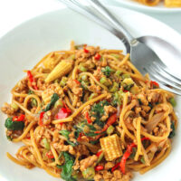 """Two diagonally placed white round plates with spaghetti tossed with ground chicken, garlic, red and green chilies, onion, baby corn, green beans, and holy basil in a brown sauce. Fork and spoon on the top corner of the front plate. Text overlay """"Thai Basil Chicken Spaghetti""""."""