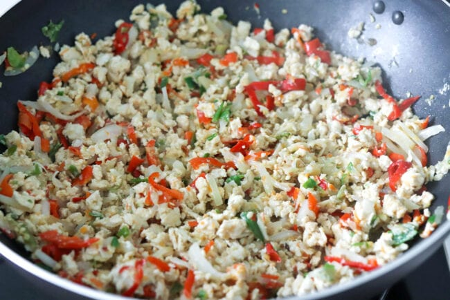Stir-fried ground chicken with onion, garlic, red and green chilies in a wok.