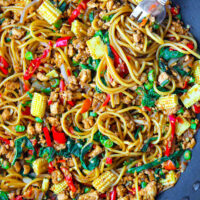 """Top Front view of a large wok with Thai Basil Chicken Spaghetti and a fork twirled around spaghetti in the top right corner. Text overlay """"Thai Basil Chicken Spaghetti""""."""