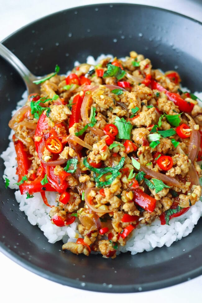 Ground pork stir-fry with onion, chilies, red bell pepper, mint leaves, and coriander in a black bowl with rice and a spoon.