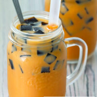 "Front view of two mason mugs with Thai milk tea, cubed grass jelly, and ice with straws and tall spoons. Text overlay ""Thai Iced Milk Tea with Grass Jelly""."