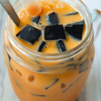 "Close up top view of a mason mug with Thai milk tea, grass jelly cubes, ice, boba straw, and a tall spoon. Text overlay ""Thai Iced Milk Tea with Grass Jelly""."