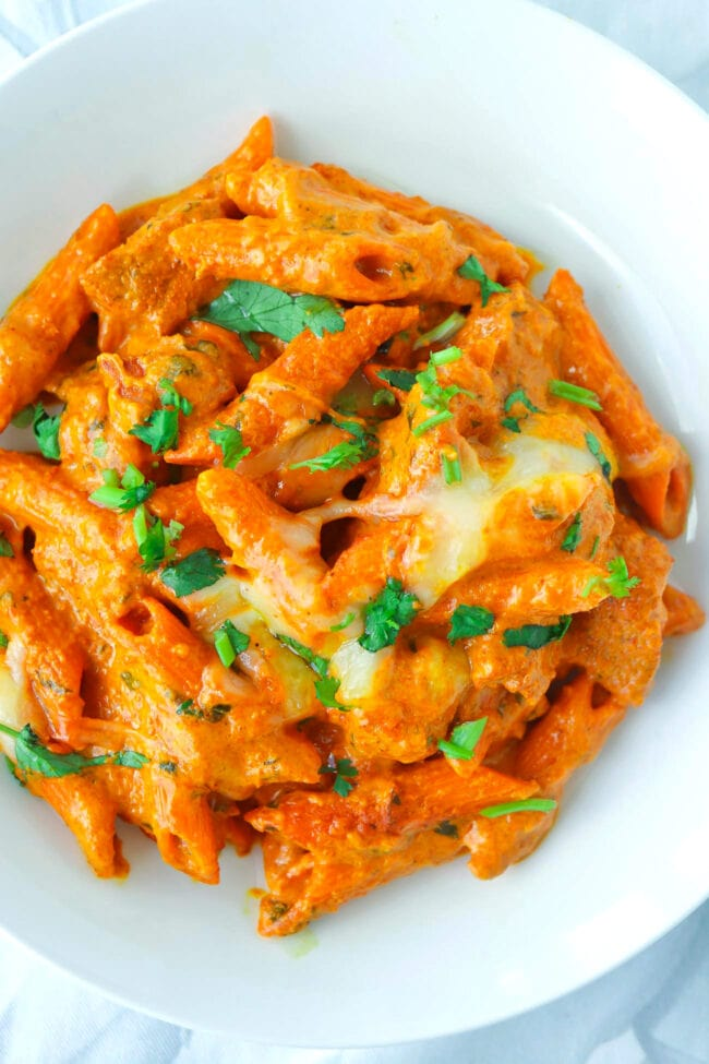 OVerhead view of Butter Chicken Pasta garnished with chopped coriander on a white plate.