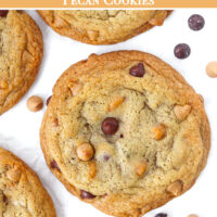 """Top view of cookies on parchment paper surrounded by a few chocolate and butterscotch chips. Text overlay """"Soft & Chewy Chocolate Butterscotch Chip Pecan Cookies""""."""
