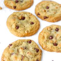 """Front view of six chocolate butterscotch chip pecan cookies on crinkled parchment paper surrounded by chocolate and butterscotch chips. Text overlay """"Soft & Chewy Chocolate Butterscotch Chip Pecan Cookies""""."""
