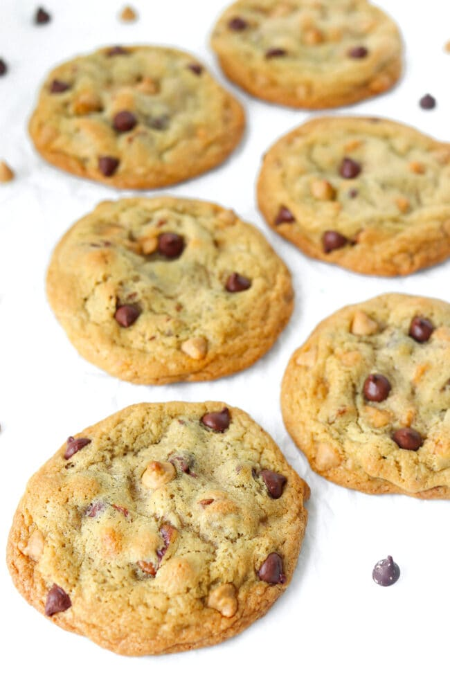 Front view of six chocolate butterscotch chip pecan cookies on crinkled parchment paper surrounded by chocolate and butterscotch chips.