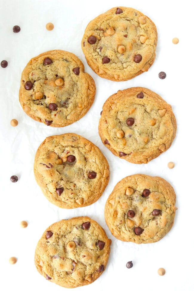 Top view of six chocolate butterscotch chip pecan cookies on crinkled parchment paper surrounded by chocolate and butterscotch chips.
