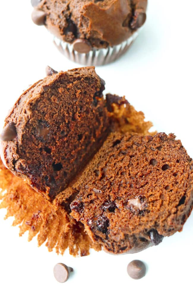 Muffin sliced in half and resting on top of muffin liner to show inside with melty chocolate chips.