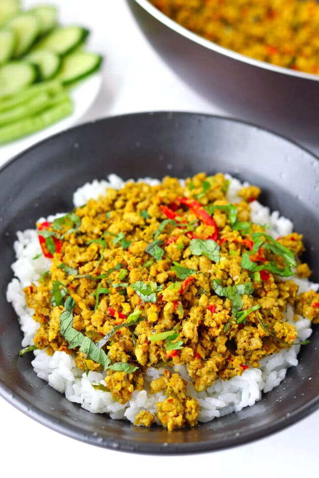 Front view of ground pork stir-fry garnished with coriander on rice in black bowl.