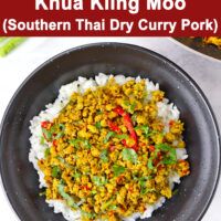 """Top view of minced pork stir-fry on rice in black bowl. Text overlay """"Khua Kling Moo (Southern Thai Dry Curry Pork)""""."""