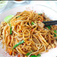 """Chopsticks tucked into stir-fried thin rice noodles with pork and vegetables on a plate. Lime wedge and crushed peanuts on side of the plate. Text overlay """"Spicy Pork Pad Thai""""."""