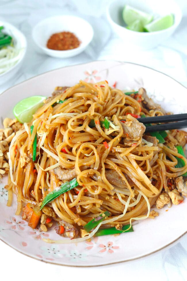 Chopsticks tucked into stir-fried thin rice noodles with pork and vegetables on a plate. Lime wedge and crushed peanuts on side of the plate.