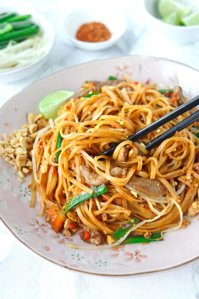 """Stir-fried noodles with black chopsticks on pink plate. Text overlay """"Spicy Pork Pad Thai""""."""