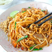 """Chopsticks tucked into stir-fried thin rice noodles with pork, veggies, a lime wedge, and crushed peanuts on a plate. Text overlay """"Spicy Pork Pad Thai""""."""