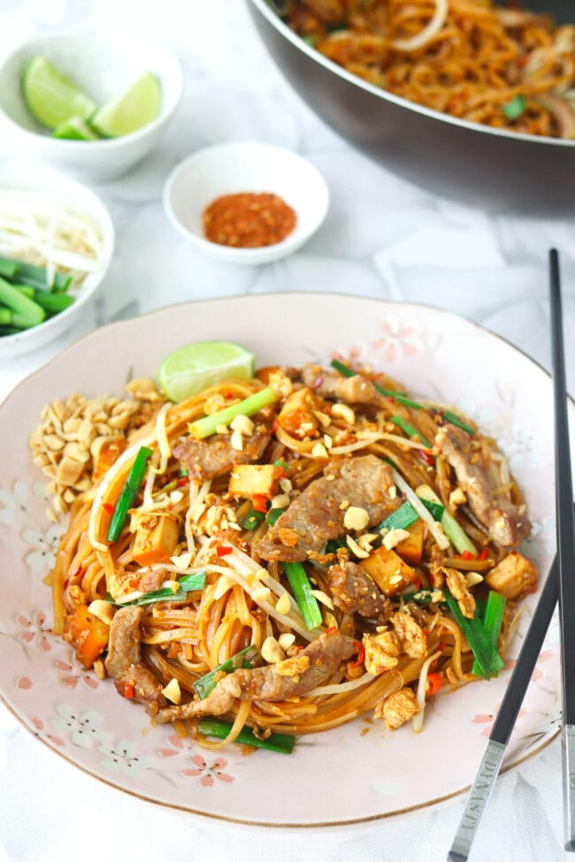 Front view of stir-fried thin rice noodles with seared pork slices on a plate with crushed peanuts, chopsticks, and a lime wedge. Wok with noodles, and small bowls with lime wedges, bean sprouts and Chinese chives, and ground hot pepper behind.