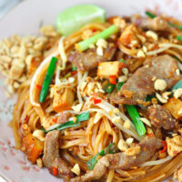 """Close up left side front view of pork and thin rice noodles garnished with chopped peanuts on plate. Text overlay """"Spicy Pork Pad Thai""""."""