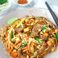 """Front view of pork Pad Thai sprinkled with chopped peanuts on a plate with a lime wedge on the side. Ground chili pepper flakes, and bean sprouts and chopped Chinese chives in small bowls in the back. Text overlay """"Spicy Pork Pad Thai""""."""