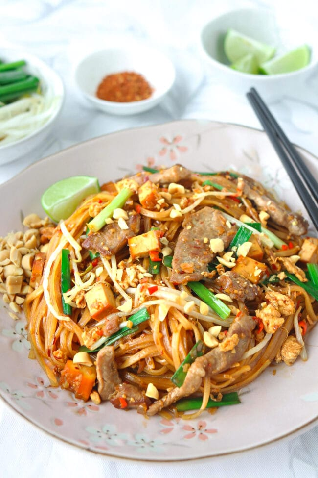 Front view of pork Pad Thai sprinkled with chopped peanuts on a plate with a lime wedge on the side. Ground chili pepper flakes, lime wedges, and bean sprouts and chopped Chinese chives in small bowls in the back.