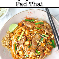 """Top view of plate with stir-fried thin rice noodles with seared pork slices, tofu, bean sprouts, crushed peanuts, lime wedge, and chopsticks. Text overlay """"Spicy Pork Pad Thai""""."""
