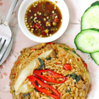 """Close up top view of fried rice, cucumber slices on pink plate, fish sauce with chilies in small dish on a plate. Text overlay """"Spicy Thai Basil Chicken Fried Rice""""."""