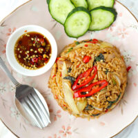 """Top view of fried rice, cucumber slices, fish sauce with chopped chilies in small dish, and spoon and fork on a plate. Text overlay """"Spicy Thai Basil Chicken Fried Rice"""" and """"thatspicychick.com""""."""