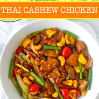 """Top view of stir-fry chicken dish with bell peppers and cashews in a serving bowl, and two bowls with rice. Text overlay """"Thai Cashew Chicken""""."""
