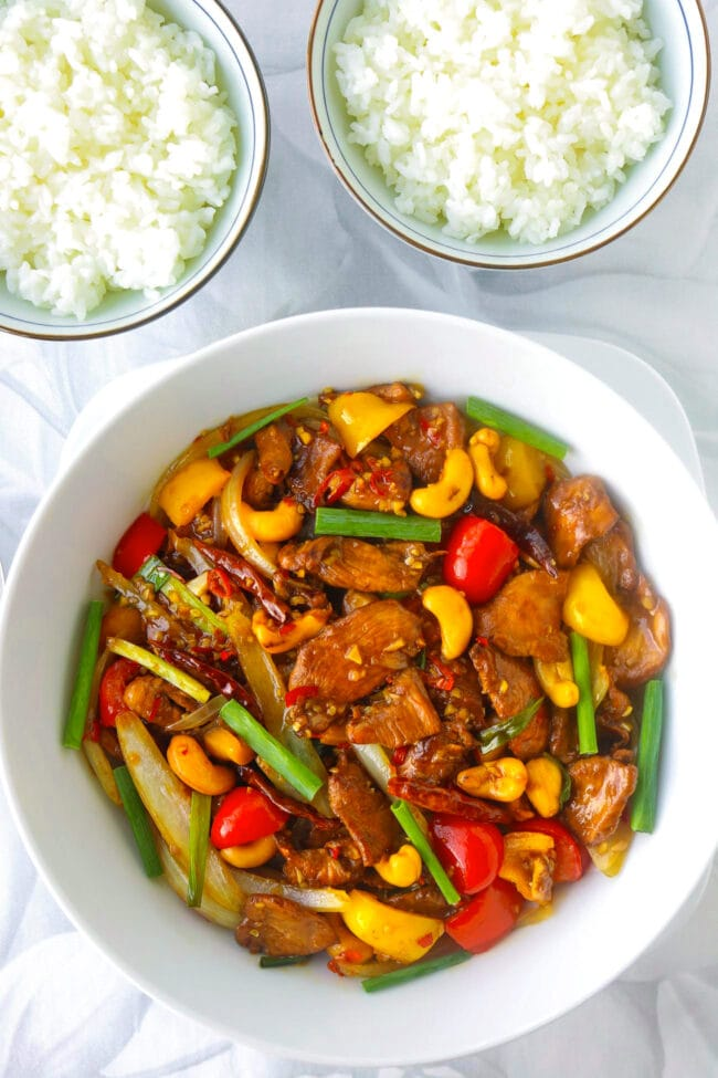 Top view of stir-fry chicken dish with bell peppers and cashews in a serving bowl, and two bowls with rice.
