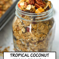 """Front view of overfilled mason jar with granola, and scattered clusters around jar. Text overlay """"Tropical Pecan Coconut Granola"""", """"Easy"""", """"Customizable"""", and """"Refined Sugar Free""""."""