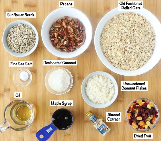 Labeled ingredients for Tropical Pecan Coconut Granola on wooden board.