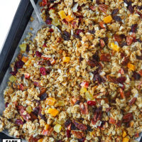 """Granola with pecans, coconut flakes, and dried fruit and spoon on parchment paper lined baking tray. Text overlay """"Tropical Pecan Coconut Granola"""", """"Easy"""", """"Customizable"""", and """"Refined Sugar Free""""."""