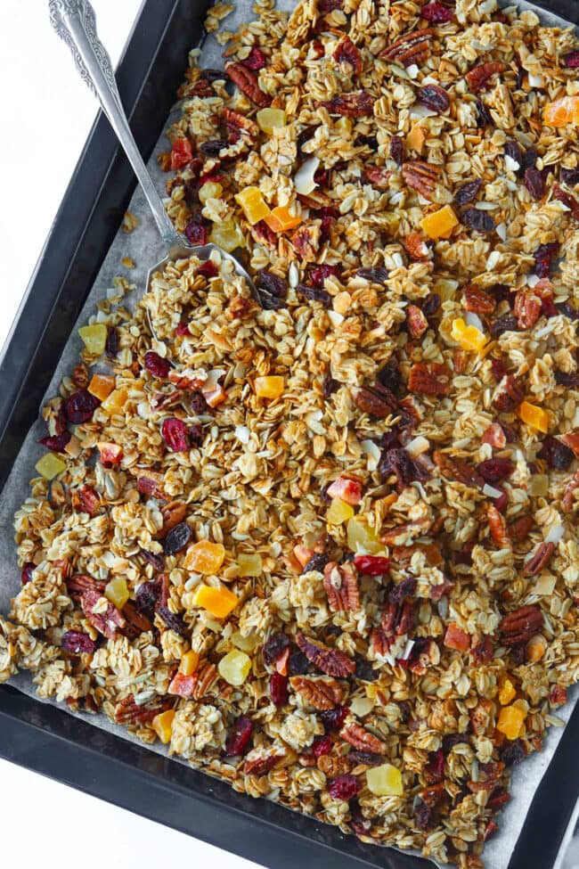 Granola with pecans, coconut flakes, and dried fruit and spoon on parchment paper lined baking tray.