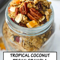 """Close up top front view of granola in mason jar, and baking tray with granola in the back. Text overlay """"Tropical Pecan Coconut Granola"""", and """"Easy - Customizable - Refined Sugar Free""""."""