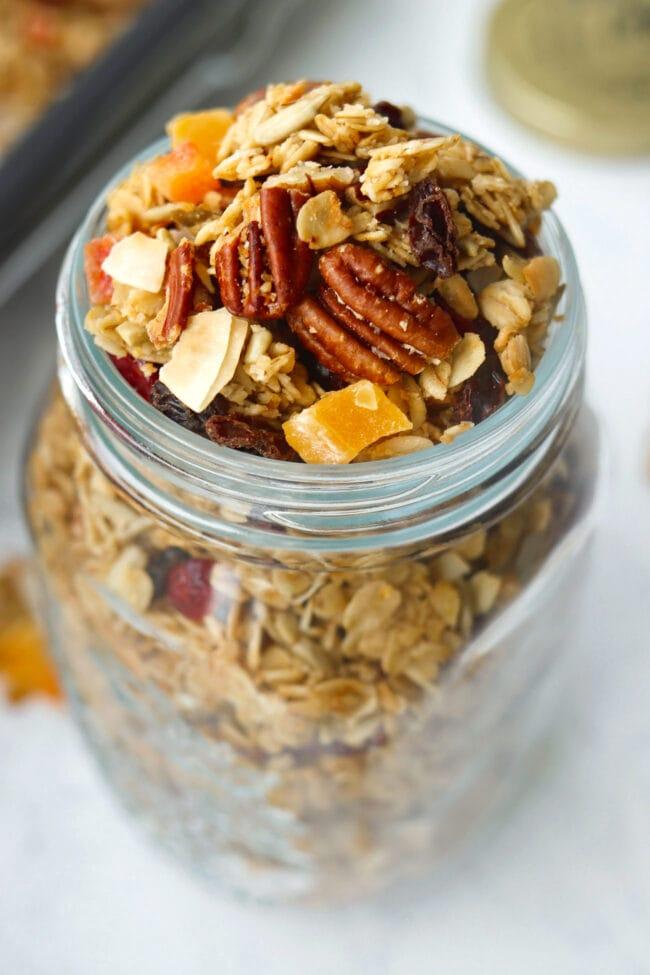 Close up top view of granola in mason jar and baking tray with granola behind.