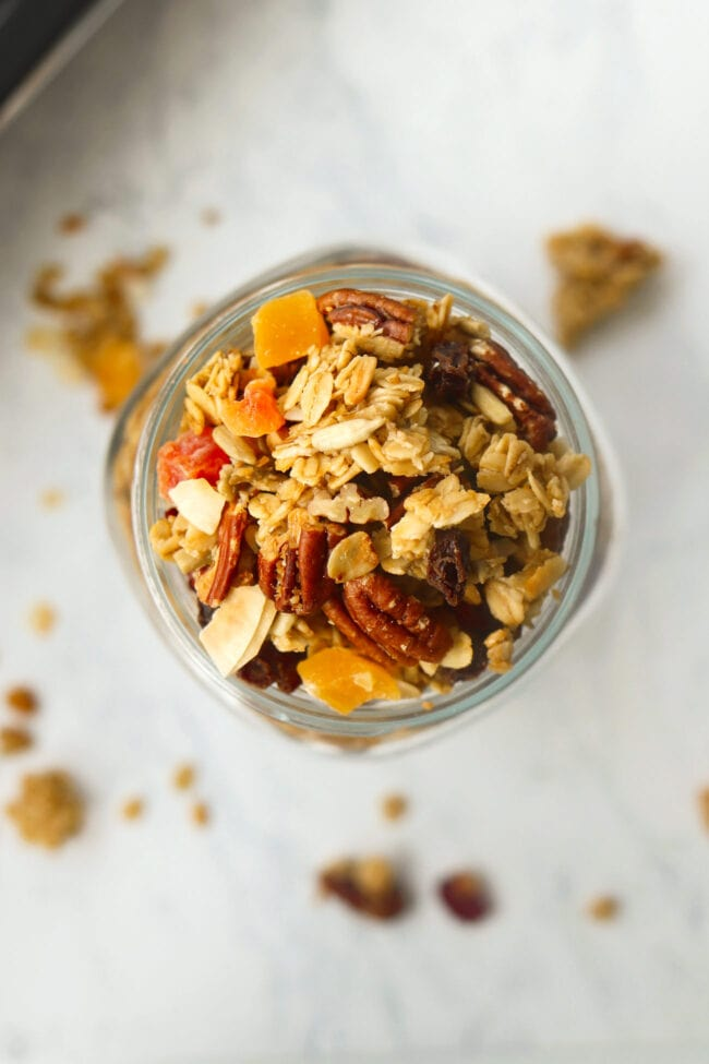 Top view of granola in mason jar surrounded by clusters on backdrop.
