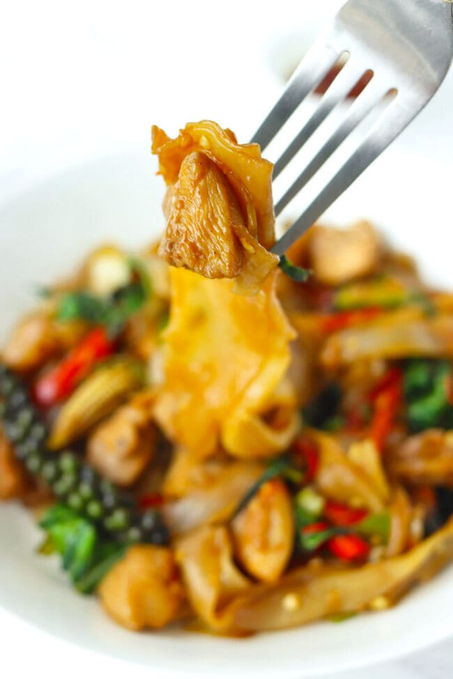 Fork holding up chicken piece and noodle strands above plate with stir-fried rice noodles dish.