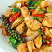 """Close up front view of stir-fried rice noodles with chicken on a plate. Text overlay """"Pad Kee Mao Gai Thai Drunken Noodles with Chicken""""."""