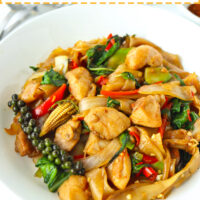 """Stir-fried rice noodles with chicken and basil dish on a plate. Text overlay """"Pad Kee Mao Gai"""", """"Thai Drunken Noodles with Chicken"""", and """"thatspicychick.com""""."""