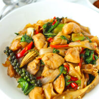 """Front view of plate with stir-fried rice noodles with chicken dish. Text overlay """"Pad Kee Mao Gai"""" and """"Thai Drunken Noodles with Chicken""""."""