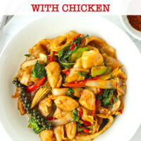 """Top view of stir-fried fresh flat wide rice noodles with chicken on a plate. Text overlay """"Pad Kee Mao Gai Thai Drunken Noodles with Chicken""""."""