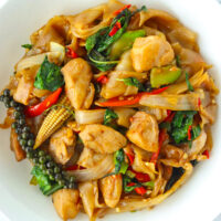 Close up top view of plate with stir-fried fresh flat wide rice noodles dish with chicken and holy basil.