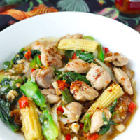 """Front view of fresh flat wide rice noodles dish with chicken, veggies, and gravy on plate. Text overlay """"Rad Na Gai (Thai Gravy Noodles with Chicken)"""""""