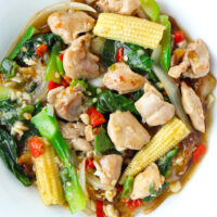 """Top view of fresh flat wide rice noodles dish with chicken, veggies, and gravy on plate on wood background. Text overlay """"Rad Na Gai (Thai Gravy Noodles with Chicken)"""""""
