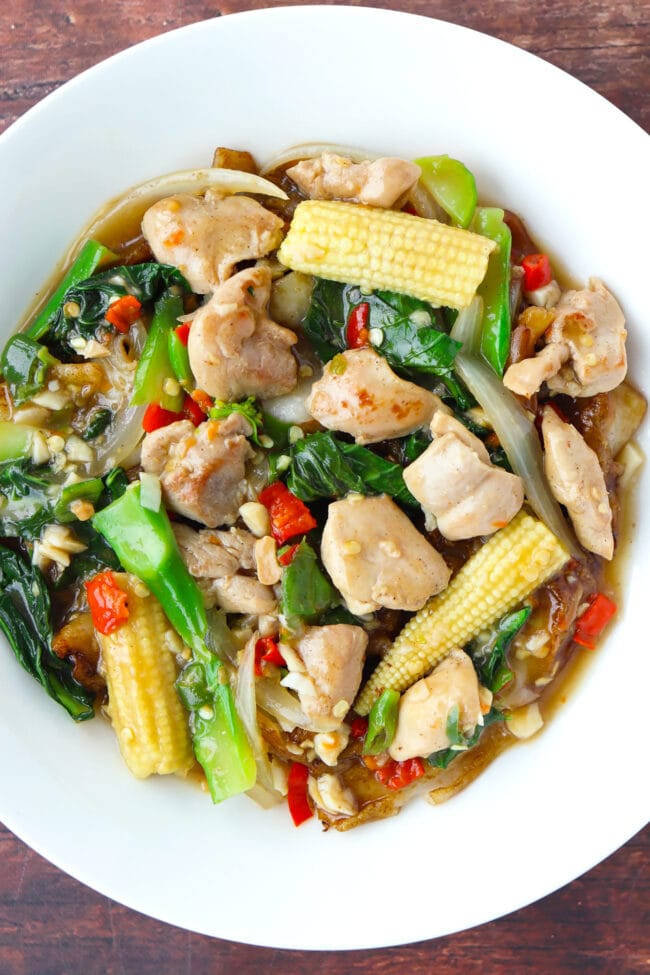 Top view of fresh flat wide rice noodles with gravy, chicken, and veggies on a plate on wooden background.