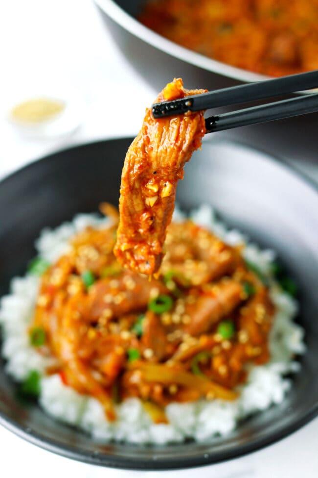 Chopsticks holding up a pork strip above bowl with pork stir-fry and rice.