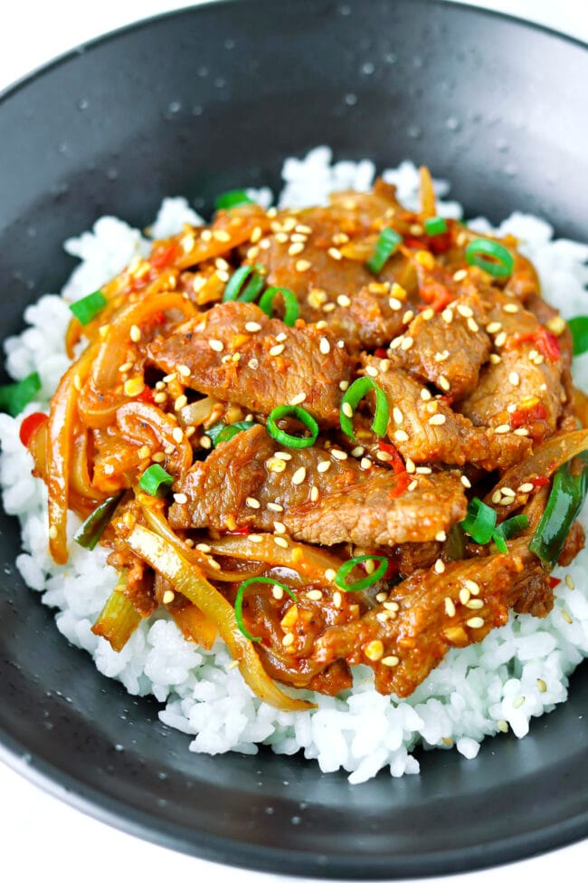 Close up front view of black bowl with spicy pork stir-fry on rice.